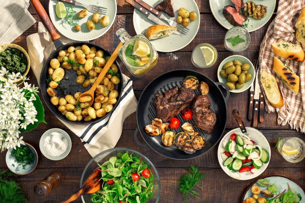 Dinner table with a spread of different foods such as grilled steak, potatoes, salad and bread sitting on a brown table.