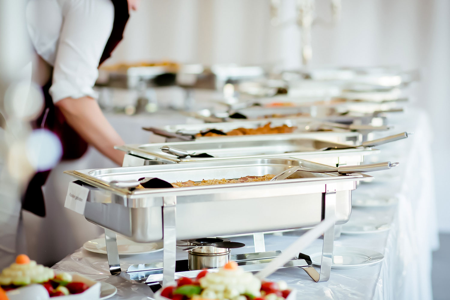 Five silver chafing dishes lined up with a server preparing to serve food.