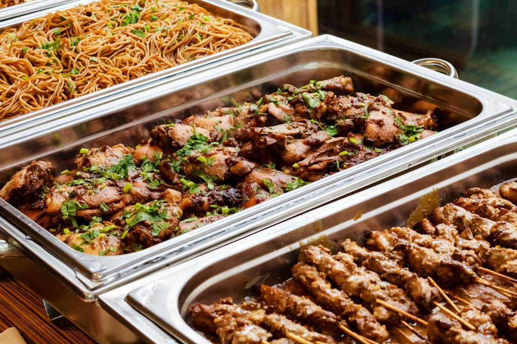 Three chafing dishes containing noodles, chicken skewers and grilled chicken thighs topped with parsley.